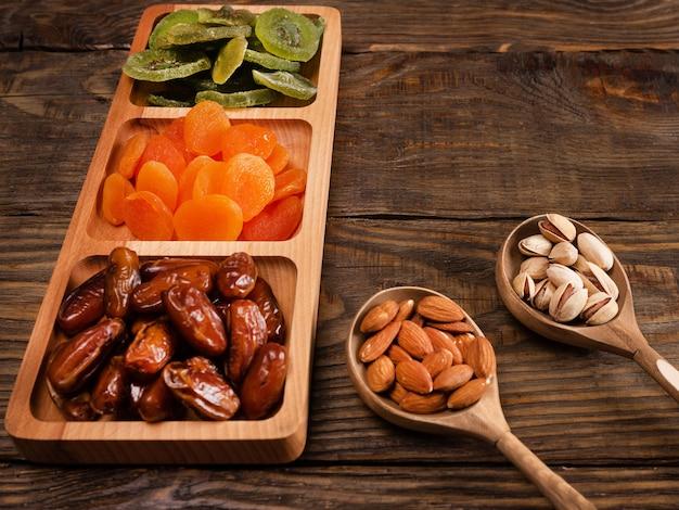 Dadels, gedroogde abrikozen en kiwi's in een compartimentenschaal en noten in een houten lepel op een donkere houten tafel.
