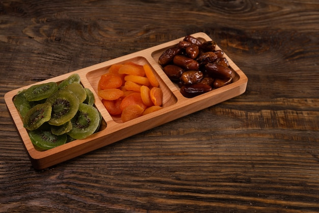 Dadels, gedroogde abrikozen en kiwi's in een compartimentenschaal op een donkere houten tafel.