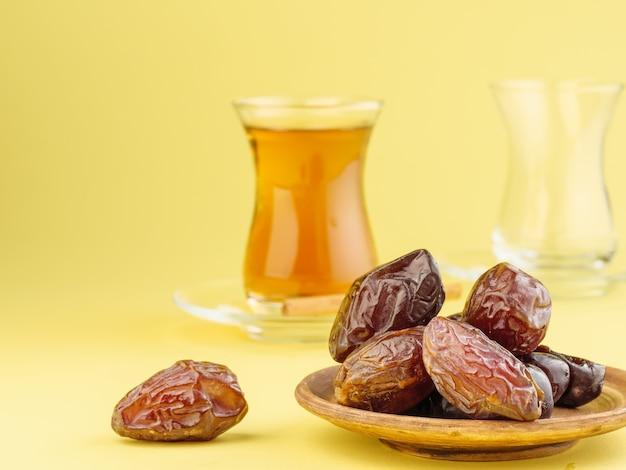 Dadels met zwarte thee op een gele achtergrond. traditioneel iftar-eten tijdens ramadan.