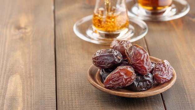 Dadels met zwarte thee op een houten tafel. traditioneel iftar-eten tijdens ramadan.