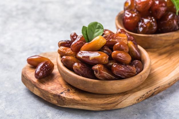 Dadels of dattes palmfruit in houten kom is een gezonde snack.