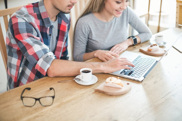 Dag in café. close up van jong koppel in café met stijlvol interieur. studenten met heerlijke koffiedrankjes. ze chatten, gebruiken laptop en glimlachen