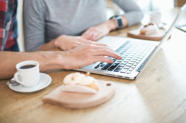 Dag in café. close up van jong koppel in café. studenten met heerlijke koffiedrankjes. ze gebruiken een laptop