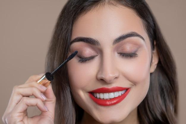 Dag make-up. gelukkig lachend mooie jonge vrouw met heldere lippen wimpers kleuren met zwarte mascara