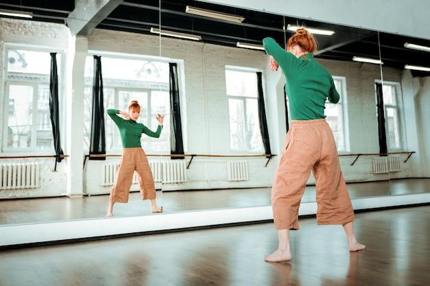 Dag op een dansschool. jonge roodharige dansleraar met een haarknotje kijkt gefocust terwijl ze haar dag in de studio doorbrengt