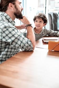 Dag samen. bebaarde vader en schattige zoon gevoel gelukkig dag doorbrengen samen zitten in restaurant