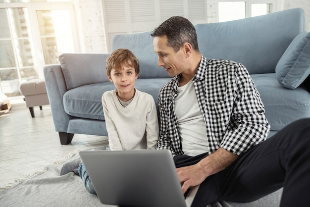 Dag samen. knappe waakzame blonde jongen glimlachend en zittend op de vloer met zijn vader en zijn vader met een laptop en kijken naar zijn zoon