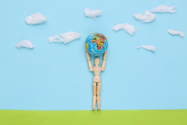 Dag van de aarde. houten pop houdt de planeet aarde vast op een met de hand gemaakt veld van blauwe lucht met wolken