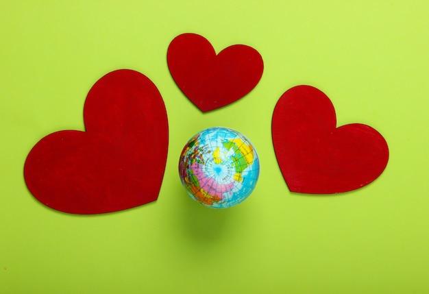Dag van de aarde. wereldbol met hartjes op een green.