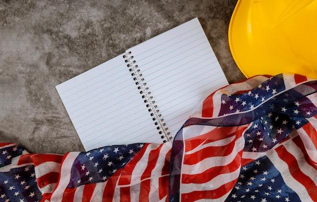 Dag van de arbeid concept gele helm op de nationale vlag van de vs