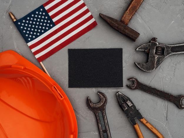 Dag van de arbeid. handgereedschap en de vlag van de verenigde staten van amerika liggend op de tafel. van bovenaf bekijken, close-up. proficiat aan familie, kennissen, vrienden en collega's. nationaal vakantieconcept