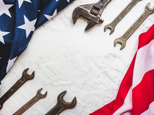 Dag van de arbeid. handgereedschap en de vlag van de verenigde staten van amerika liggend op de tafel. van bovenaf bekijken, close-up. proficiat aan familie, verwanten, vrienden en collega's. nationaal vakantieconcept