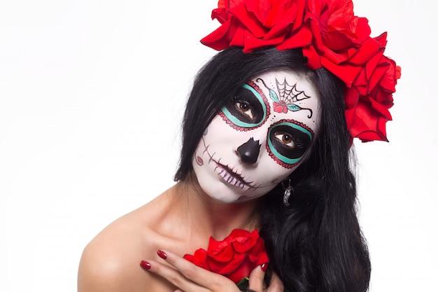 Dag van de doden. halloween. jonge vrouw in de dag van de dode masker schedel gezicht kunst en roos. geïsoleerd op wit. detailopname.