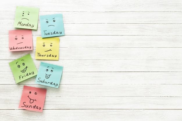 Dag van de week en gezichtsuitdrukking. gekleurde stickers op een lichte houten achtergrond