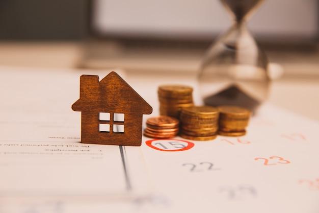 Dag van kopen of verkopen van een huis. dag van betaling voor huur of lening. kalender en huis. het is tijd om uw huis te verzekeren. lege ruimte voor tekst.