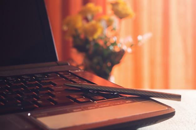 Dagboek en labtop voor werk aan houten tafel met bloem en rood gordijn, notitieboekje, boek, pen, dagboek, klok.