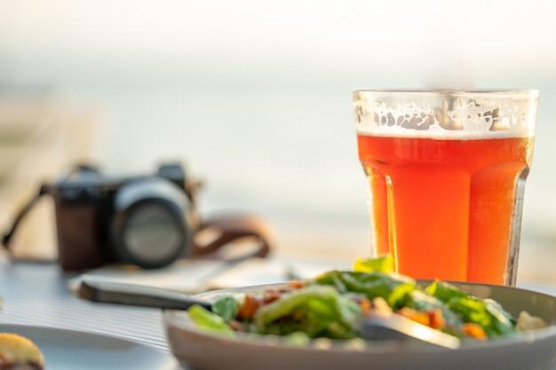 Dagboek met pen en salades geplaatst op de strandtafel. de vacante kant