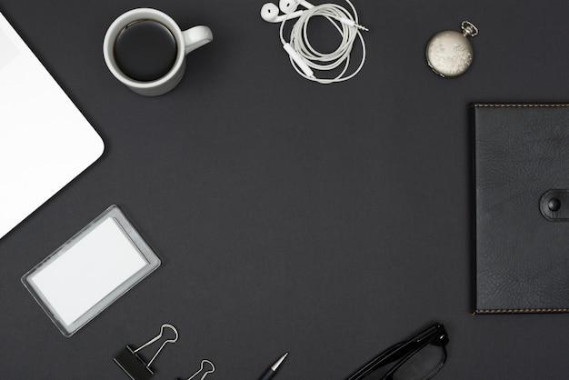 Dagboek; oortelefoon; koffiekop; laptop; paperclips; bril op zwarte desktop