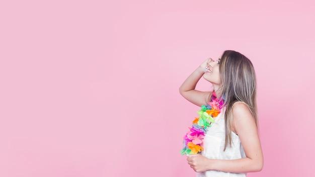 Dagdromen jonge vrouw op roze achtergrond