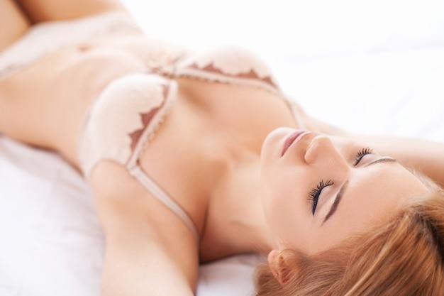 Dagdromen. mooie jonge vrouw in lingerie die in bed ligt en ogen gesloten houdt