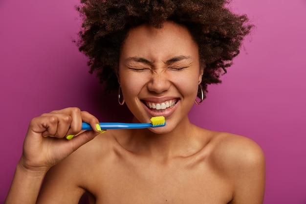 Dagelijks leven, ochtendroutine en tandenreinigingsconcept. horizontale opname van shirtless donkere huid vrouw tanden poetsen met tandenborstel, staat naakt tegen paarse muur, in goed humeur