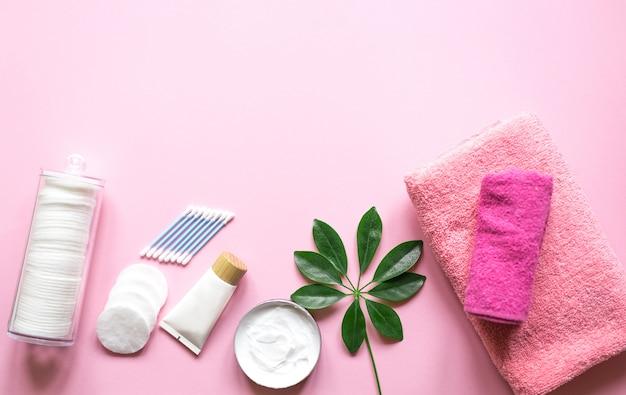 Dagelijkse hygiëneproducten met wattenschijfje, handdoek, crème en lotion op roze tafel met bovenaanzicht