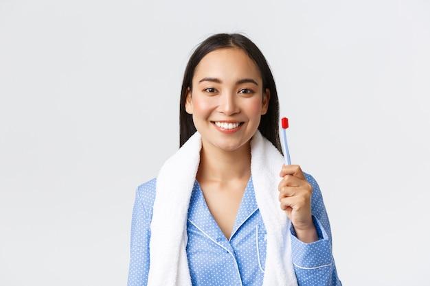 Dagelijkse routine, ochtend- en hygiëneconcept. vrij aziatisch meisje in blauwe pyjama, handdoek vasthoudend en tandenborstel tonend, witte tanden glimlachen, zich klaarmaken voor het douchen voor het slapengaan, witte achtergrond