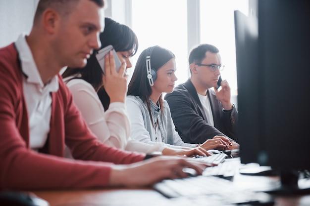 Dagelijkse routineklus. jonge mensen die in het callcenter werken. er komen nieuwe deals aan