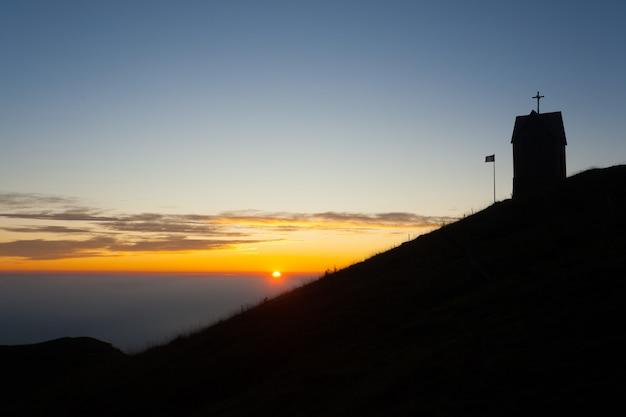 Dageraad bij het kerkje, mount grappa landschap, italië. italiaans alpenpanorama