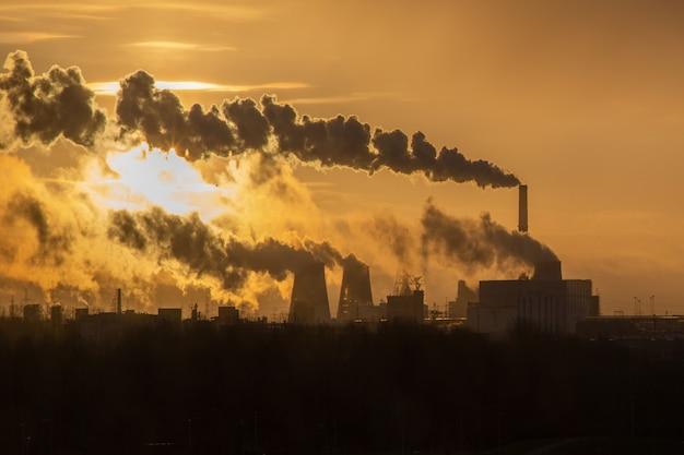 Dageraad boven de rokende schoorstenen warmtekrachtcentrale