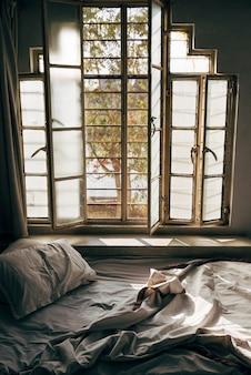 Daglicht schijnt door een onopgemaakt bed