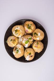 Dahi puri is een snack die populair is in de staat maharashtra, india. dit gerecht valt onder de categorie chat. geserveerd in een rond bord op een kleurrijke of houten ondergrond. selectieve focus