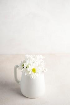 Daisy bloemen in kruik op tafel