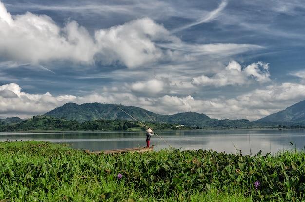 Dak lak- viet nam: groep van aziatische boer gaan werken per roeiboot op het meer van lak in de herfsttijd