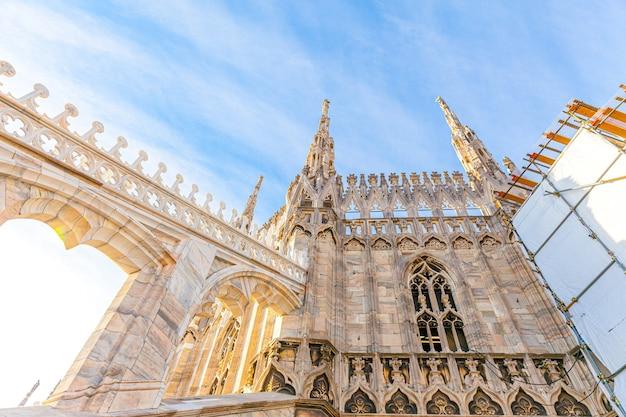 Dak van de dom van milaan duomo di milano met gotische torenspitsen en witmarmeren standbeelden op piazza in milaan
