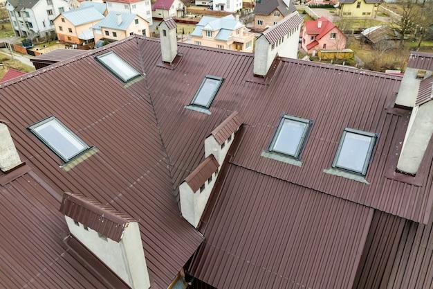 Dak van een huis gemaakt van metalen platen met zolderramen.