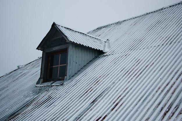 Dak van het gebouw bedekt met sneeuw tegen de bewolkte hemel
