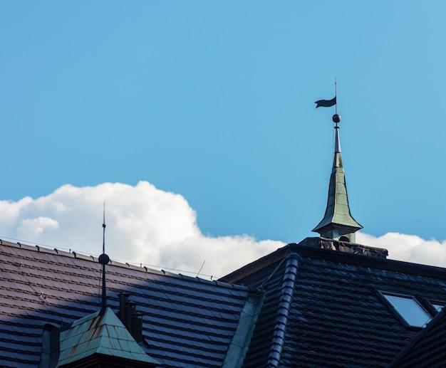 Dak van huis in renaissancestijl met blauwe hemel