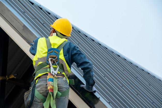 Dakdekker bezig met dakconstructie, dakdekker die metalen plaat op bovendak installeert.