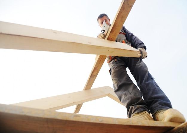 Dakdekker die houten bouw voor het huis voorbereiden