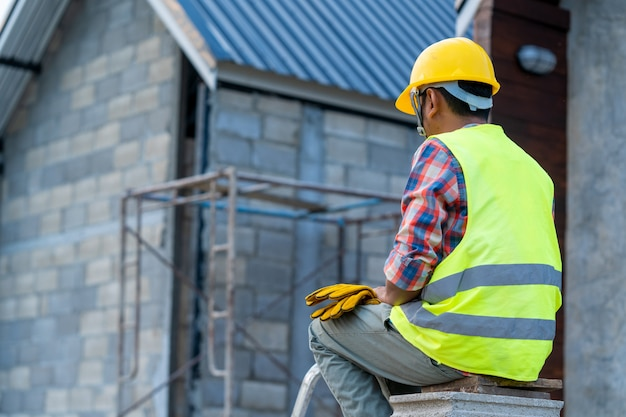 Dakdekker die veiligheidsgordelriem draagt tijdens het werken aan dakstructuur van het voortbouwen op bouwwerf.