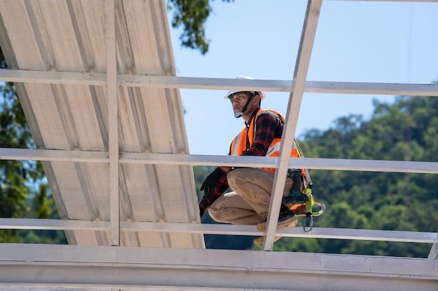 Dakdekker die werkt bij de installatie van metalen profieldaken, dakbedekkingsgereedschappen, elektrische boor gebruikt op nieuwe daken.