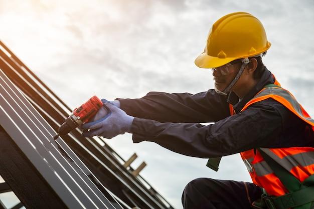 Dakdekker in beschermende uniforme slijtage en handschoenen, bouwvakker installeert nieuw dak, dakgereedschap, elektrische boor gebruikt op nieuwe daken met metalen plaat.