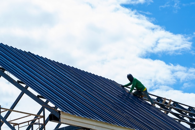 Dakdekker werknemer in beschermende uniforme slijtage en handschoenen, met behulp van lucht of pneumatische schiethamer en het installeren van asfalt grind op het nieuwe dak, concept van woningbouw in aanbouw.
