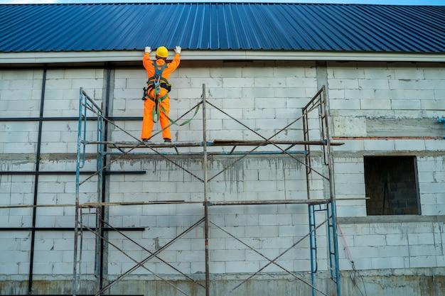 Dakdekker werknemer in beschermende uniforme slijtage en veiligheidslijn werken installeren nieuw dak op de bouwplaats.