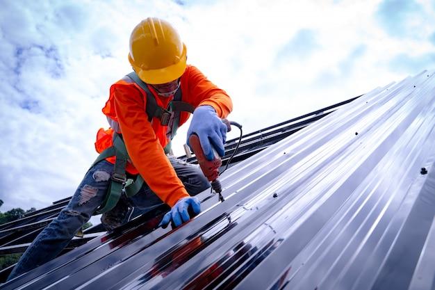Dakdekker werkt aan dakconstructie van bouwen op bouwplaats, dakdekker gebruikt lucht- of pneumatisch schiethamer en installeert metalen plaat op nieuw dak.