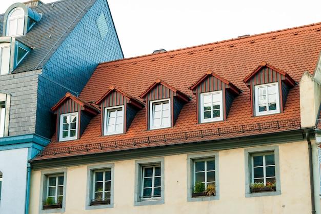 Daken van oude huizen met dakramen en oranje dakpannen in duitse stad
