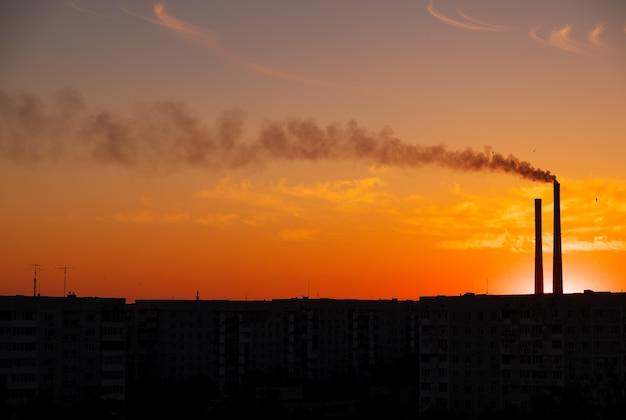 Daken van stadshuizen tijdens zonsondergang. donkere rook uit de pijp van de thermische elektriciteitscentrale.