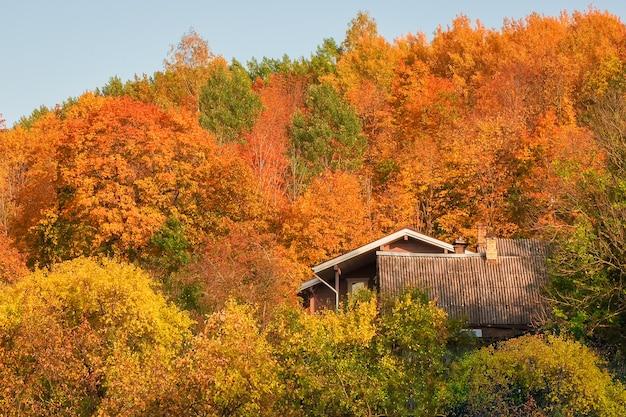 Dakhuis op een heuvel omringd door kleurrijk herfstgebladerte.