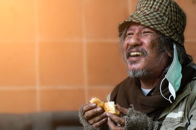 Dakloos en hongerig. sluit omhoog van hogere mens die brood eet